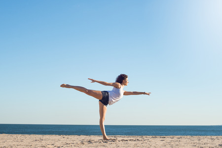 Photo pour Young woman performing yoga on the beach during a beautiful morning. Beautiful young woman stretching during yoga on the beach. Young woman balancing on one leg in yoga stretch position at the beach. - image libre de droit
