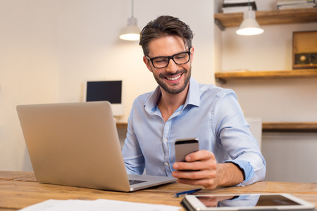 Photo pour Young happy businessman smiling while reading his smartphone. Portrait of smiling business man reading message with smartphone in office. Man working at his desk at office. - image libre de droit