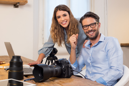 Photo for Professional photographers with camera and laptop computer working at studio. Photographer with assistant sitting in office and looking at camera. Team of photographers working together. - Royalty Free Image