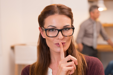 Photo pour Portrait of an attractive business woman with finger on lips. Young businesswoman with eyeglasses in office asking for silence while team working in the background. Woman with finger on lips gesturing for quite. - image libre de droit