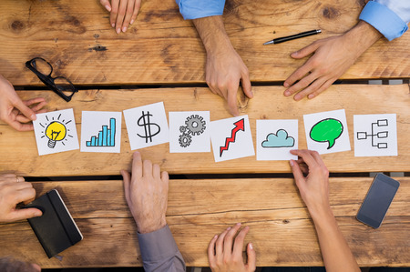Photo pour Businesspeople arranging different business concepts on wooden table. White cards strategy used by businesspeople. Business people brainstoring for new solutions while placing different cards in office. - image libre de droit