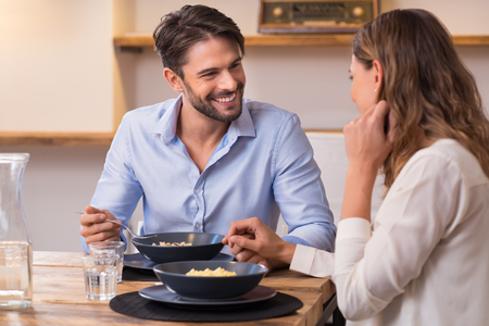 Foto de Loving couple looking at each other while having lunch. Close up shot of young man and woman having dinner at home. Happy young couple eating. - Imagen libre de derechos