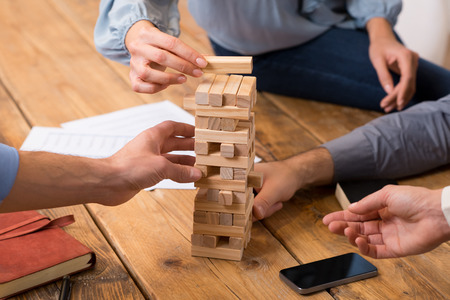 Foto de Close up of hands helping build a building of wooden pieces. Businesspeople planning a new business strategy. Business team trying to generate new ideas with the help of playing with wooden bricks. Business risk concept. - Imagen libre de derechos