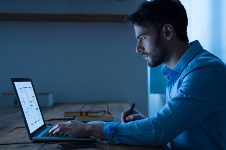 Photo for Architect sitting at night working on architectural plan on laptop. Young handsome interior designer in casual checking blueprint of a house on laptop. Architect studying the map and layout of a new project. - Royalty Free Image