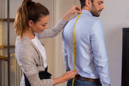 Photo pour Tailor standing near male client measuring back. Tailor woman taking measures for new business shirt using tape meter. Young fashion designer taking measurement of man wearing shirt in store. - image libre de droit