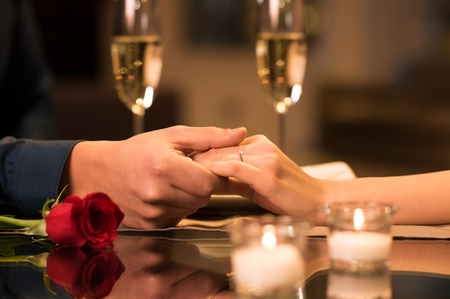Foto de Closeup of couple hands on restaurant table with two glasses of champagne in background. - Imagen libre de derechos