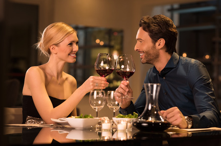 Photo pour Couple toasting wine glasses during a romantic dinner in a gourmet restaurant. - image libre de droit