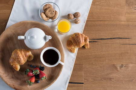 Photo for Healthy breakfast with brioche, orange juice, chocolate cookies, berries, tea and walnuts with copy space. - Royalty Free Image