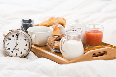 Photo pour Healthy breakfast served on a tray on bed with alarm clock. - image libre de droit