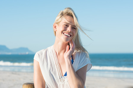 Photo pour Portrait of happy smiling woman on the beach. Smiling sensual blonde posing on a beautiful wild beach. Pretty girl in casaul looking away and laughing. - image libre de droit