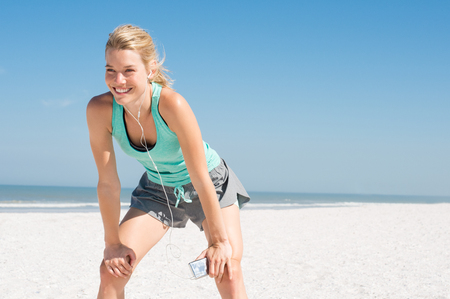 Photo for Young happy athlete tired after exercising. Woman resting at beach and listening to music after a routine workout. Young woman enjoying music at beach after run. - Royalty Free Image