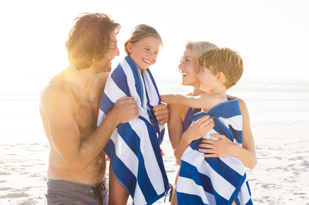 Photo pour Wet son and daughter draped in towel embracing by parents after swim. Happy family at beach after swim in the tropical sea. Smiling father and mother drying children with a towels. - image libre de droit