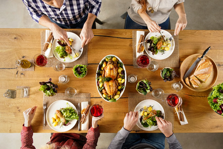 Foto per Top view of dining table with salad and roasted chicken with potatoes. High angle view of happy young friends having lunch at home. Men and women eating lunch together. - Immagine Royalty Free