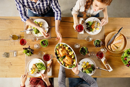 Photo for Top view of man passing food bowl to friend. High angle view of happy young friends eating together at home. Happy men and women having lunch with roasted chicken. - Royalty Free Image