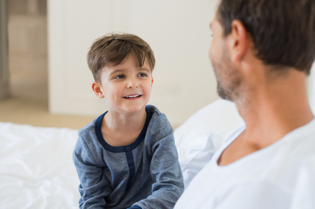 Foto de Father and son sitting on bed and talking to each other. Father and smiling little boy playing while sitting on bed. Portrait of happy child listening his father at home. - Imagen libre de derechos