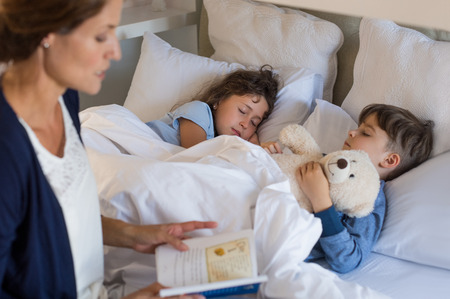 Photo pour Mother reading bed time stories to children. Brother and sister sleeping peacefully. Mother putting son and daughter to sleep. - image libre de droit