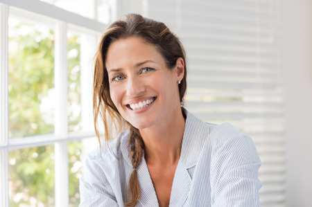 Photo pour Portrait of beautiful mature woman sitting and smiling. Woman feeling fresh on a bright sunny morning at home. Woman sitting in nightwear near the window and looking at camera. - image libre de droit