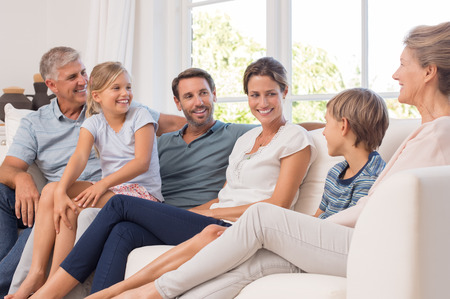 Photo pour Happy generation family sitting on couch at home and talking. Portrait of extended family group sitting together in a conversation. Smiling mother and father with children and grandparent. - image libre de droit