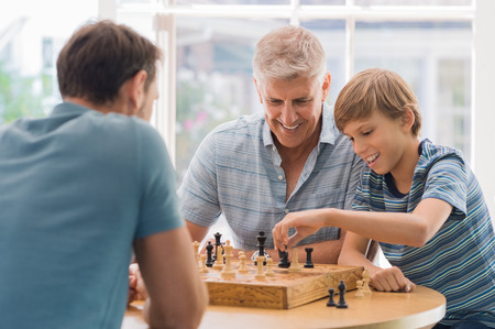 Photo pour Grandfather teaching grandson how to play chess. Father and son playing chess with grandchild. Grandfather watching son and grandson playing board game at home. - image libre de droit