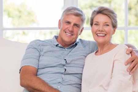 Photo pour Smiling senior woman, and man sitting together on a sofa. Portrait of a candid older couple enjoying their retirement at home. Happy smiling senior couple embracing together and looking at camera. - image libre de droit