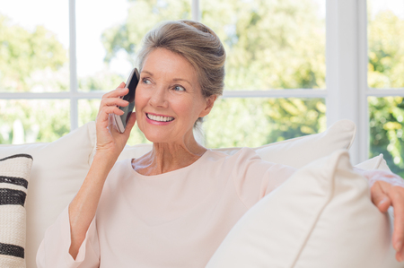 Photo pour Senior woman talking on her mobile phone. Senior woman has a happy conversation at cellphone. Smiling senior woman using phone sitting on couch at home. - image libre de droit