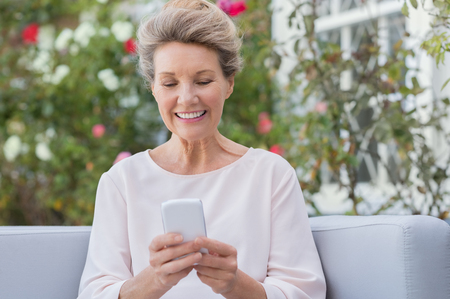 Foto de Senior woman messagging with mobile phone while sitting on sofa in the garden. Older woman texting a phone message with her new smartphone. - Imagen libre de derechos