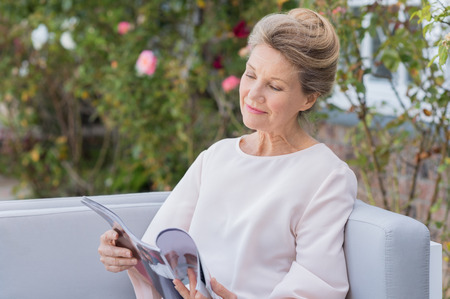 Foto per Senior woman reading a magazine sitting on a couch outdoor. Happy elderly woman reading a gossip magazine in her free time. Mature woman relaxing in the garden. - Immagine Royalty Free