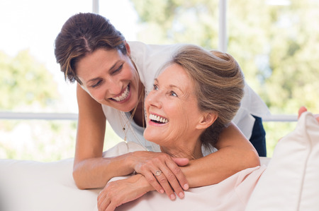 Foto de Portrait of mother and daughter hugging. Happy senior mother and adult daughter embracing at home. Cheerful woman embraces older woman and looking at each other. - Imagen libre de derechos