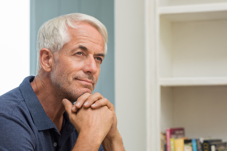 Foto de Portrait of thoughtful senior man at home. Pensive retired man smiling and looking up. Happy mature man thinking about his retirement. - Imagen libre de derechos