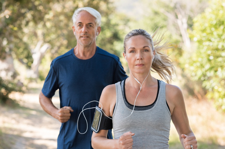 Photo pour Senior man and woman jogging in park while listening to music. Mature couple running at park together. Retired man and mid woman exercising outdoor. - image libre de droit