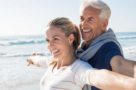 Foto de Happy senior couple standing on beach with arms outstretched and looking away. Happy couple at beach on a bright sunny day. Retired husband and smiling wife thinking about their future. - Imagen libre de derechos
