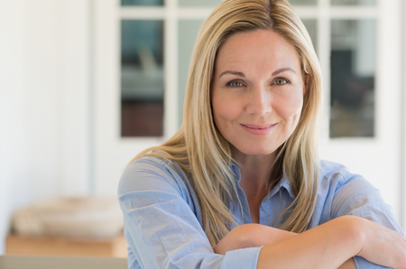 Photo pour Happy mature woman relaxing on her couch at home in the living room. Close up face of senior woman looking at camera. Portrait of happy woman in blue shirt smiling. - image libre de droit