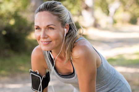 Foto de Portrait of athletic mature woman resting after jogging. Beautiful senior blonde woman running at the park on a sunny day. Female runner listening to music while jogging. - Imagen libre de derechos
