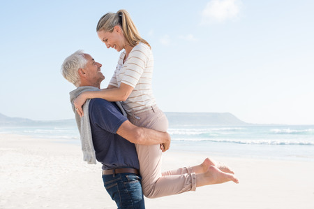 Photo for Cute senior couple hugging on the beach on a sunny day. Happy couple having fun together at the beach. Senior man carrrying her wife at beach and looking at each other. - Royalty Free Image