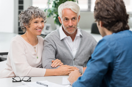 Foto de Senior couple meeting real estate agent. Senior couple meeting financial advisor for investment. Happy mature man and woman listening to various investment plans for their retirement. - Imagen libre de derechos