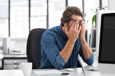 Foto de Portrait of an upset businessman at desk in office. Businessman being depressed by working in office. Young stressed business man feeling strain in eyes after working for long hours on computer. - Imagen libre de derechos