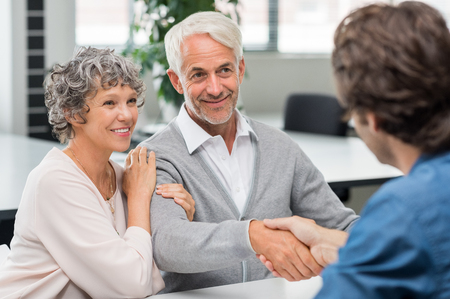 Photo pour Happy senior couple shaking hands with retirement consultant. Smiling senior man shaking hands with young businessman for business agreement. Handshake between senior man and financial agent after obtaining a loan. - image libre de droit