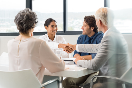 Photo for Handshake to seal a deal after a job recruitment meeting. Two successful business people shaking hands in front of their colleagues. Senior businessman shaking hands to young businesswoman in a modern office. - Royalty Free Image