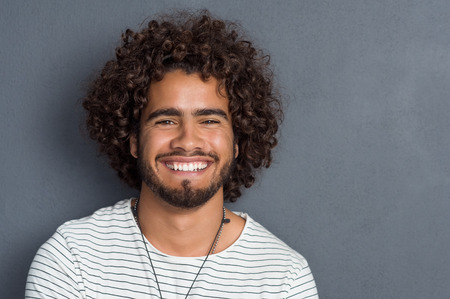 Foto de Portrait of a happy cheerful young man looking at camera. Handsome young man with beard and curly hair standing against grey background. Close up face of multi ethnic young man isolated against grey wall. - Imagen libre de derechos