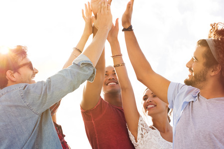 Photo pour Group of happy friends high five and having fun together. Mixed race guys and girls celebrating success. Cheerful young men and women giving high five to each other. - image libre de droit