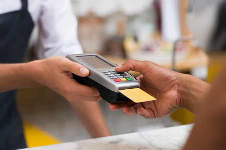 Photo pour Close up of hand using credit card swiping machine to pay. Hand with creditcard swipe through terminal for payment in cafeteria. Man entering credit card code in swipe machine. - image libre de droit