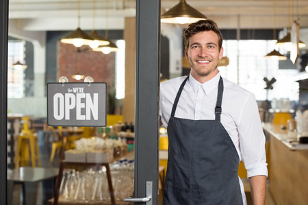 Foto de Portrait of smiling owner standing at his restaurant gate with open signboard. Young entrepreneur leaning at the cafeteria door and looking at camera. Chef or waiter standing in front of coffee shop. - Imagen libre de derechos