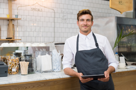 Foto de Successful small business owner holding digital tablet and looking at camera. Happy smiling waiter with apron and digital tablet leaning on counter. Portrait of young entrepreneur of coffee shop posing. - Imagen libre de derechos