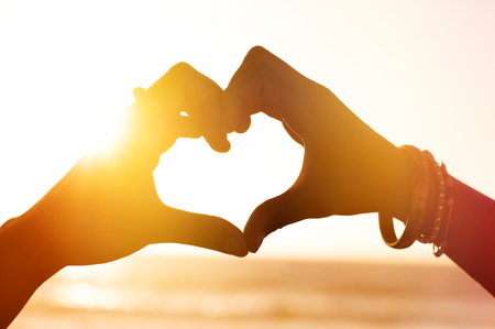 Foto de Heart shape of hands against sea during sunset. Close up of heart made of fingers at beach. Hand in shape of love heart on sunlight background, silhouette. - Imagen libre de derechos