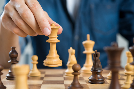 Foto de Close up of hand of man playing chess holding queen. Business man playing chess. Hand of casual businessman making a move with queen in chess. Business strategy and leadership concept. - Imagen libre de derechos