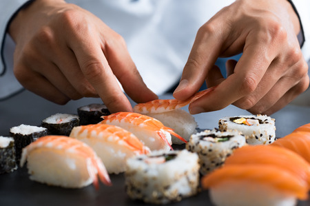 Photo for Closeup of chef hands preparing japanese food. Japanese chef making sushi at restaurant. Young chef serving traditional japanese sushi served on a black stone plate. - Royalty Free Image