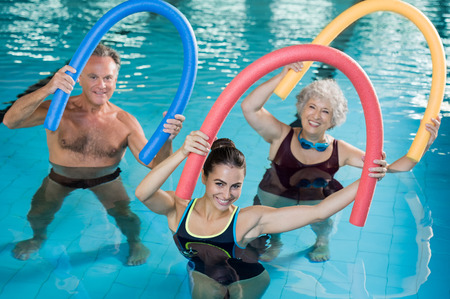 Photo for Portrait of smiling people doing aqua fitness together in a swimming pool. Group of senior woman and mature man with swim noodles exercising in a swimming pool. Young trainer and senior people in aqua gym fitness class. - Royalty Free Image