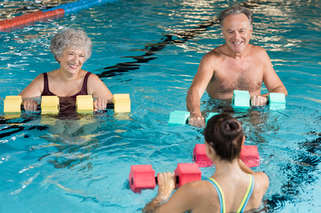 Foto de Senior couple in training session of aqua aerobics using dumbbells in swimming pool. Mature man and old woman practicing aqua fitness together. Healthy and fit senior couple enjoying their retirement in aqua aerobics training. - Imagen libre de derechos