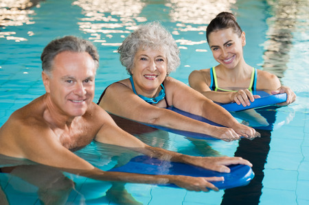 Foto de Happy senior couple taking swimming lessons from young trainer. Smiling old woman and mature man doing aqua aerobics exercise in swimming pool. Retired people in swimming pool looking at camera. - Imagen libre de derechos