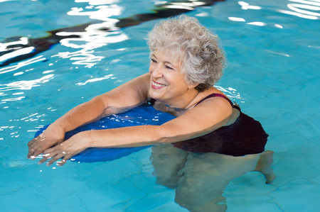 Photo pour Happy senior woman with kickboard in a swimming pool. Old woman swimming in water with the help of a kickboard. Smiling old woman swimming with inflatable board in swimming pool. - image libre de droit